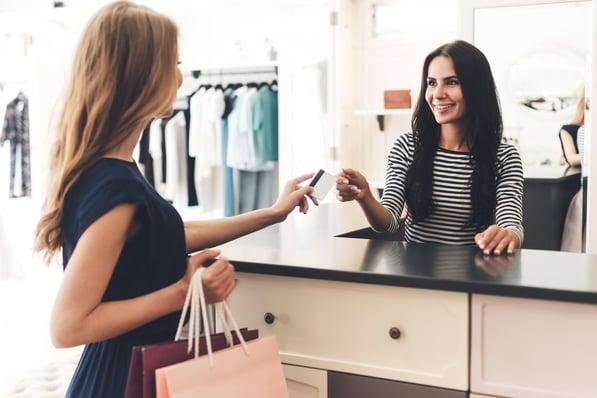 A shopper handing a store clerk her credit card.