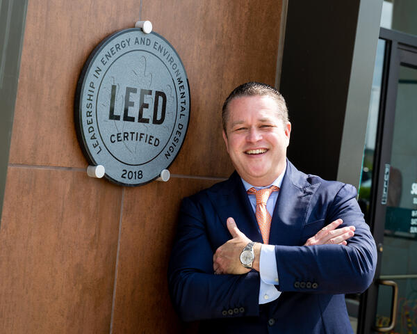 Abe Pacetti posing in front of a LEED Certified plaque.