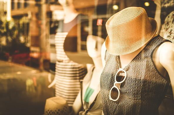 Women's clothing and hat on a mannequin in a store window.
