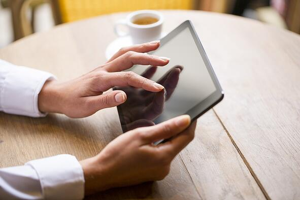 Close-up of a woman using a tablet with a cup of coffee in the background.