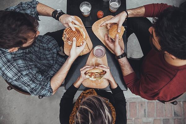 Overhead view of friends at a table, holding sandwiches.