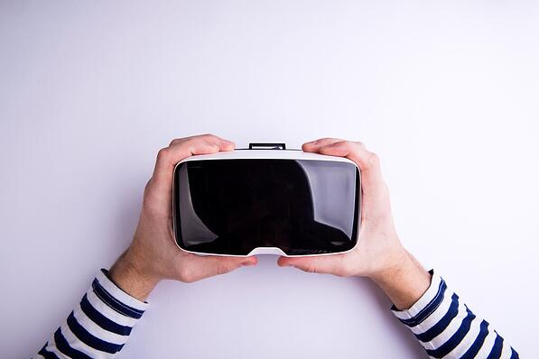 Overhead view of two hands holding a virtual reality headset.