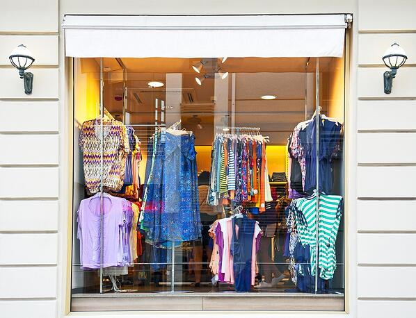 Racks of women's clothes in a store window.