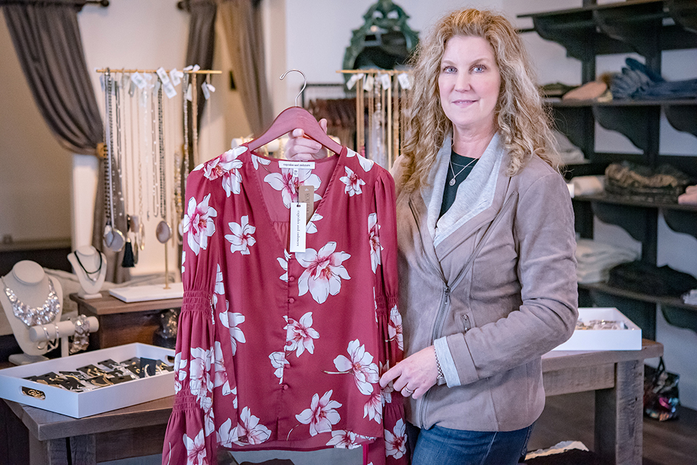 Michelle Bowers holding red and white floral long sleeve blouse while in store