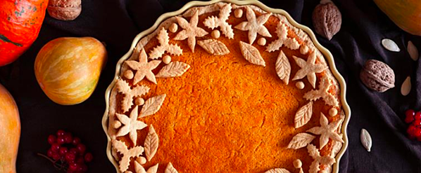 Close-up of a pumpkin pie and autumnal vegetables.