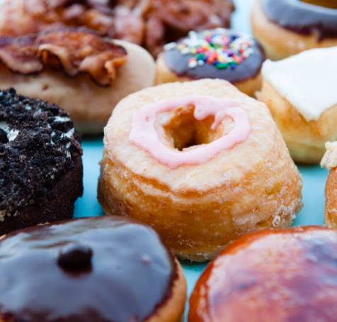 Various donuts, with one with a strip of bacon on top.