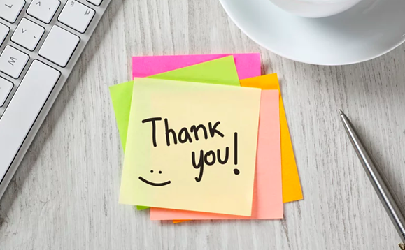 """Post-it note with """"Thank you!"""" and a smiley face written on it."""