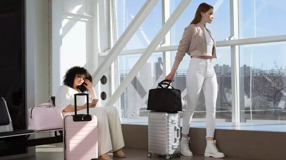 two women using Away suitcases in white and light pink at an airport