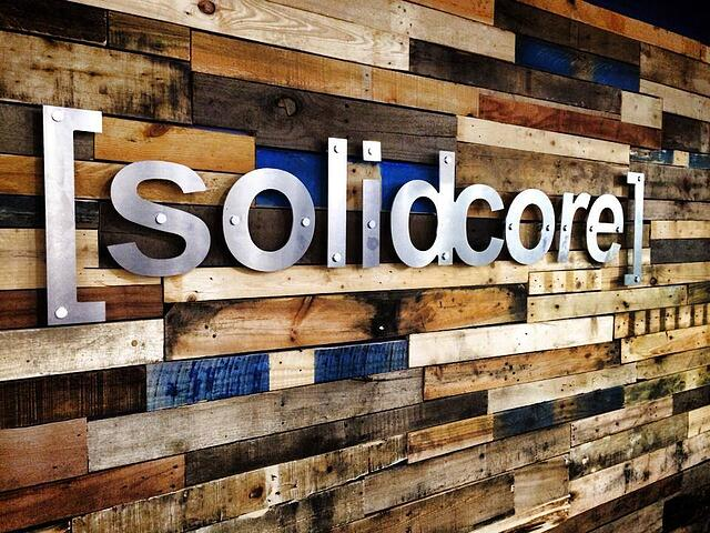 "Wooden wall with metal signage that says, ""Solidcore."""