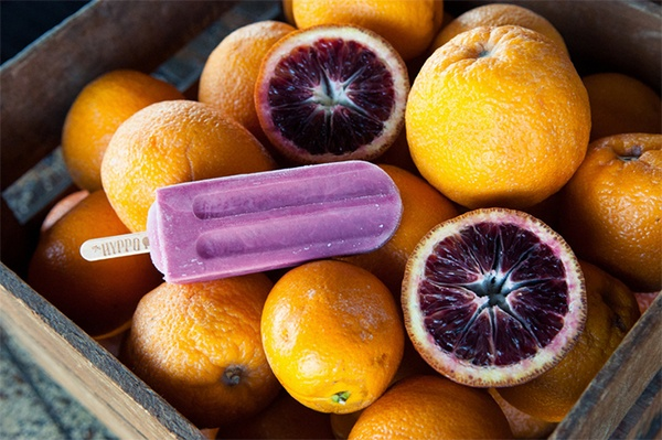 Close-up of a purple popsicle on top of many blood oranges.