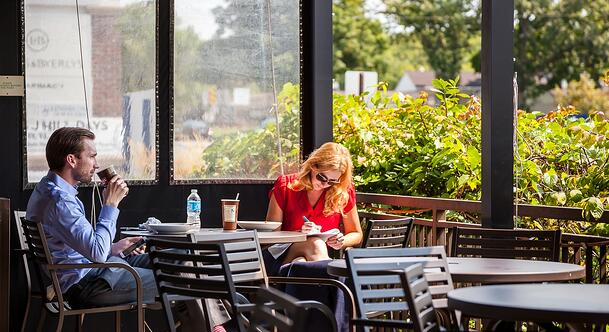 a couple sitting at an outdoor restaurant table doing work and drinking coffee