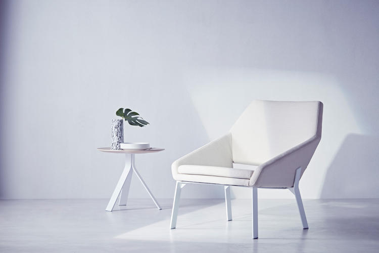 A white, modern chair next to a side table.