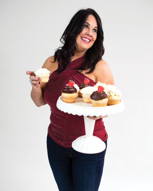 Margo Engberg posing with cupcakes.