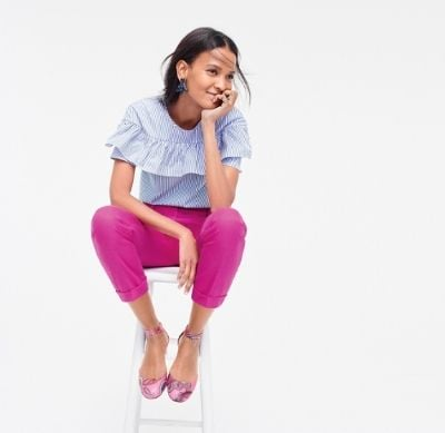 Female model wearing J.Crew clothes while sitting on a stool.