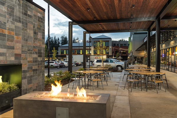 A lit fire pit next to next patio seating, with a wooden ceiling above.