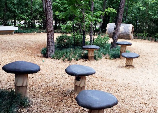Several stools in the playground made to look like mushrooms.