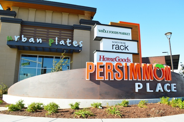 Persimmon Place signage with various store logos attached, and an Urban Plates storefront in the background.