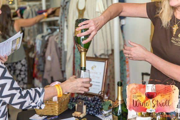 Woman at a stand pouring wine into a customer's glass.