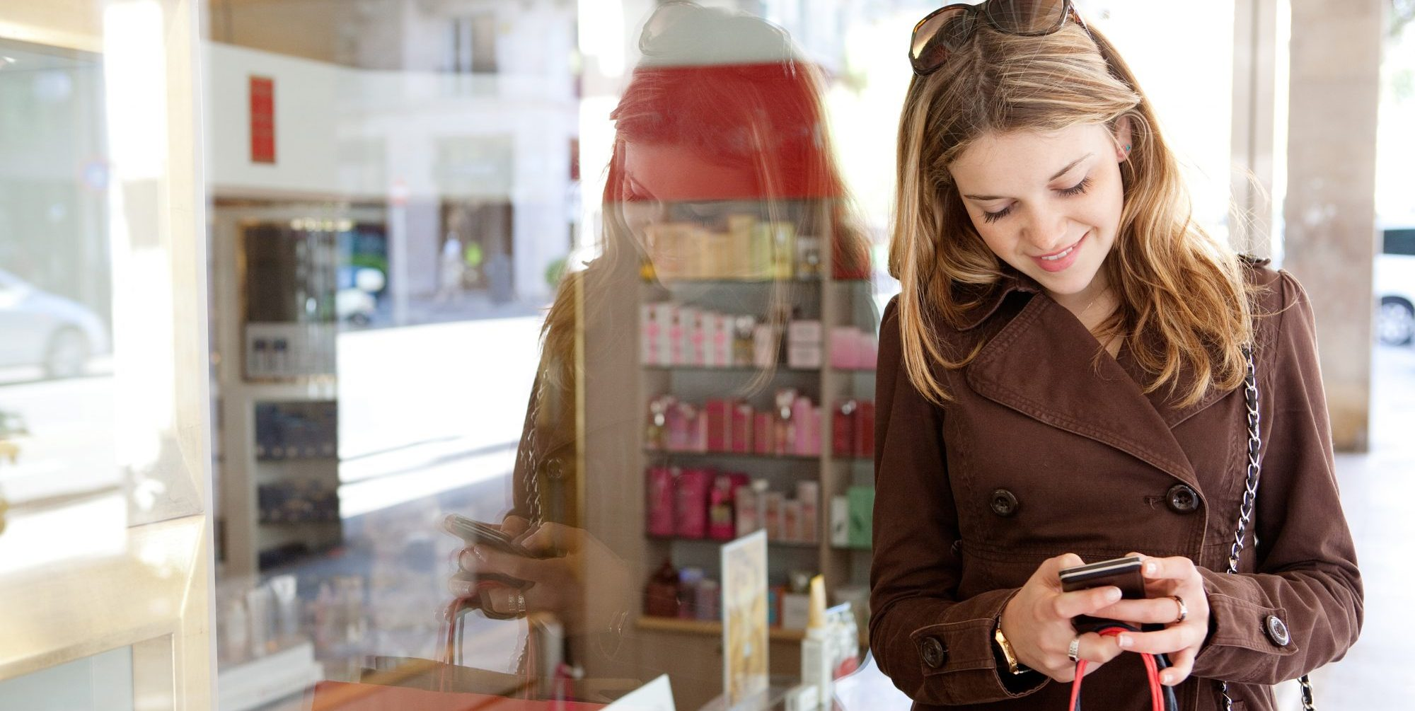 Young woman standing in front of a store while looking at her phone.