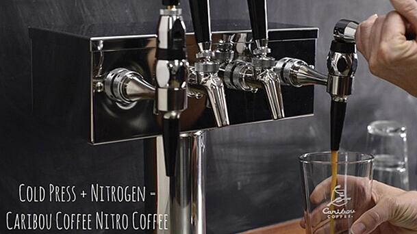 nitro coffee bar tap with coffee being poured into glass cup