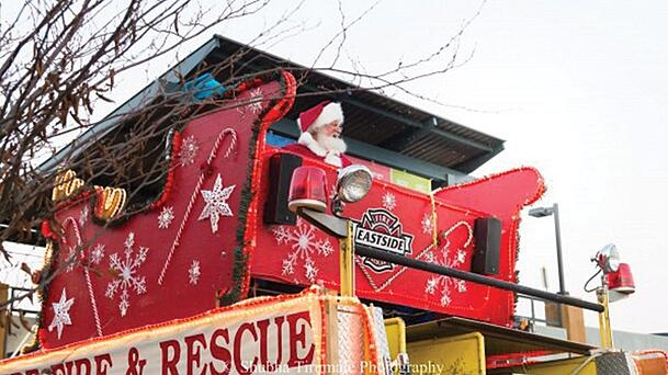 Santa sitting in a sleigh that's sitting atop a fire truck.
