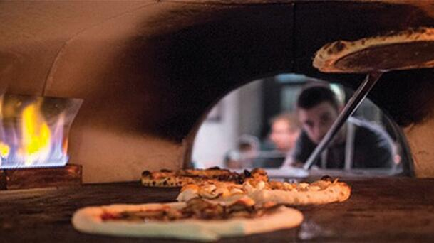 pizza being cooked inside of a wood fire grill with the chef placing another pizza in the oven
