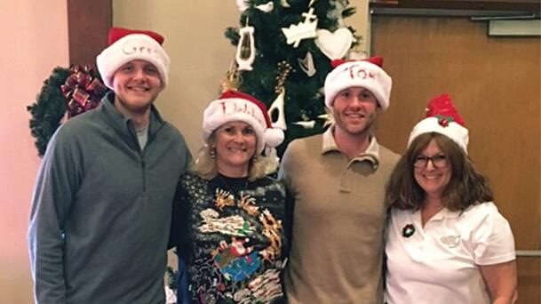 Volunteers from Regency center wearing santa hats in front of a christmas tree, posing for a picture and smiling.