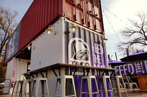 A Taco Bell made of stacked shipping containers in a public space.