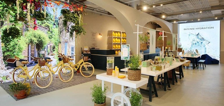 Retail space that yellow bikes, plants and an HD wall projection of a lush patio to bring the outdoors inside.