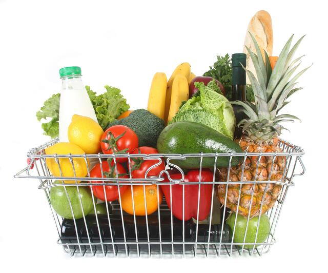 Shopping basket containing milk, break, wine and various fruits and vegetables.