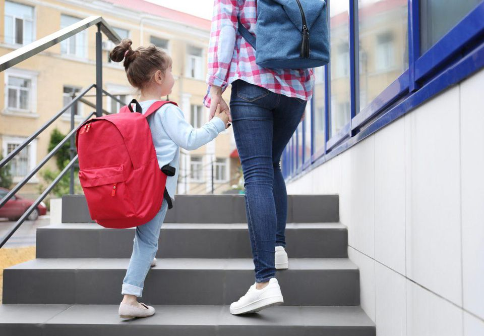 little girl with big red backpack holding hands with her mom.