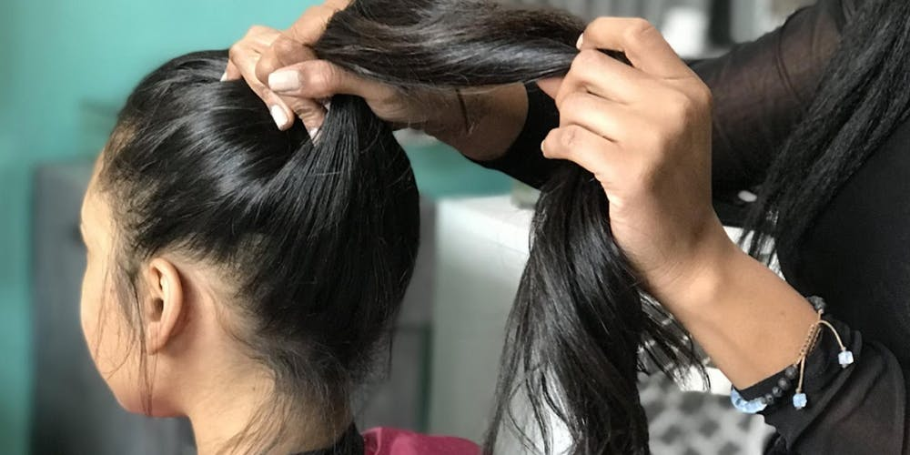 hair stylist putting customer's hair in ponytail
