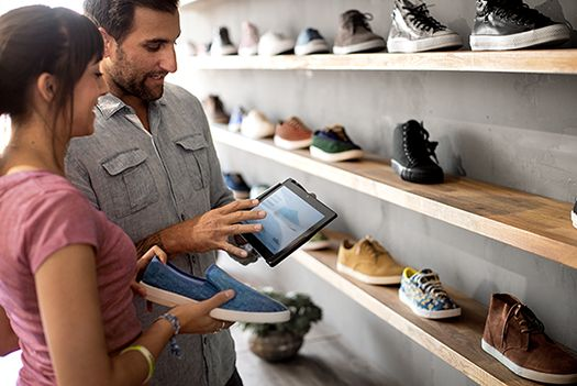 a customer in a shoe store with the employee showing them the shoe on an ipad