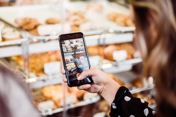 woman holding phone taking a video of a bakery display