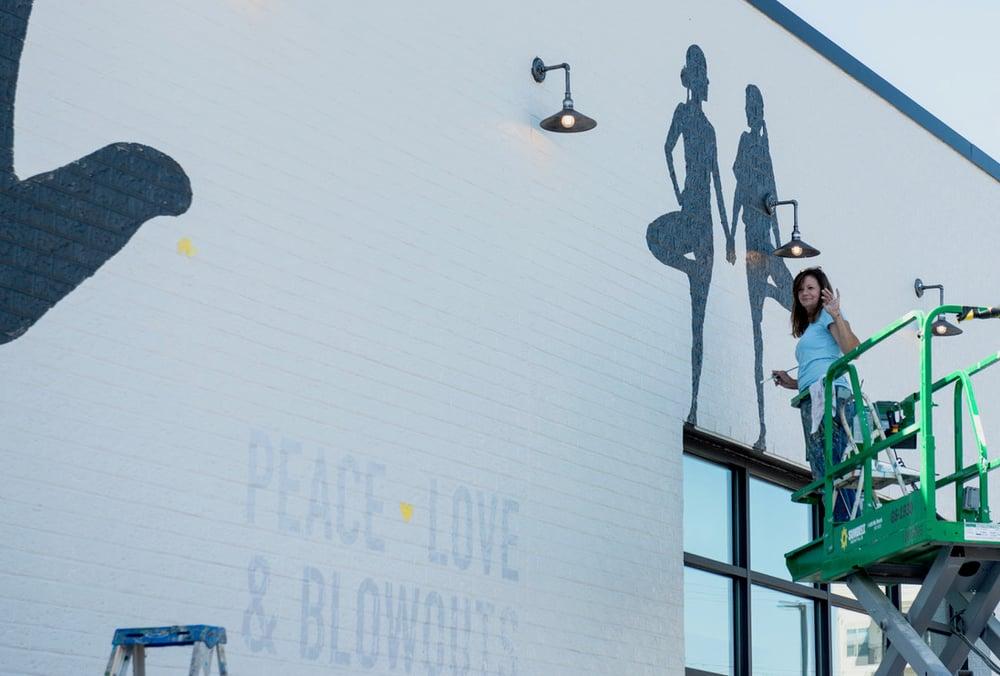 Muralist Lisa Gaither waving from forklift