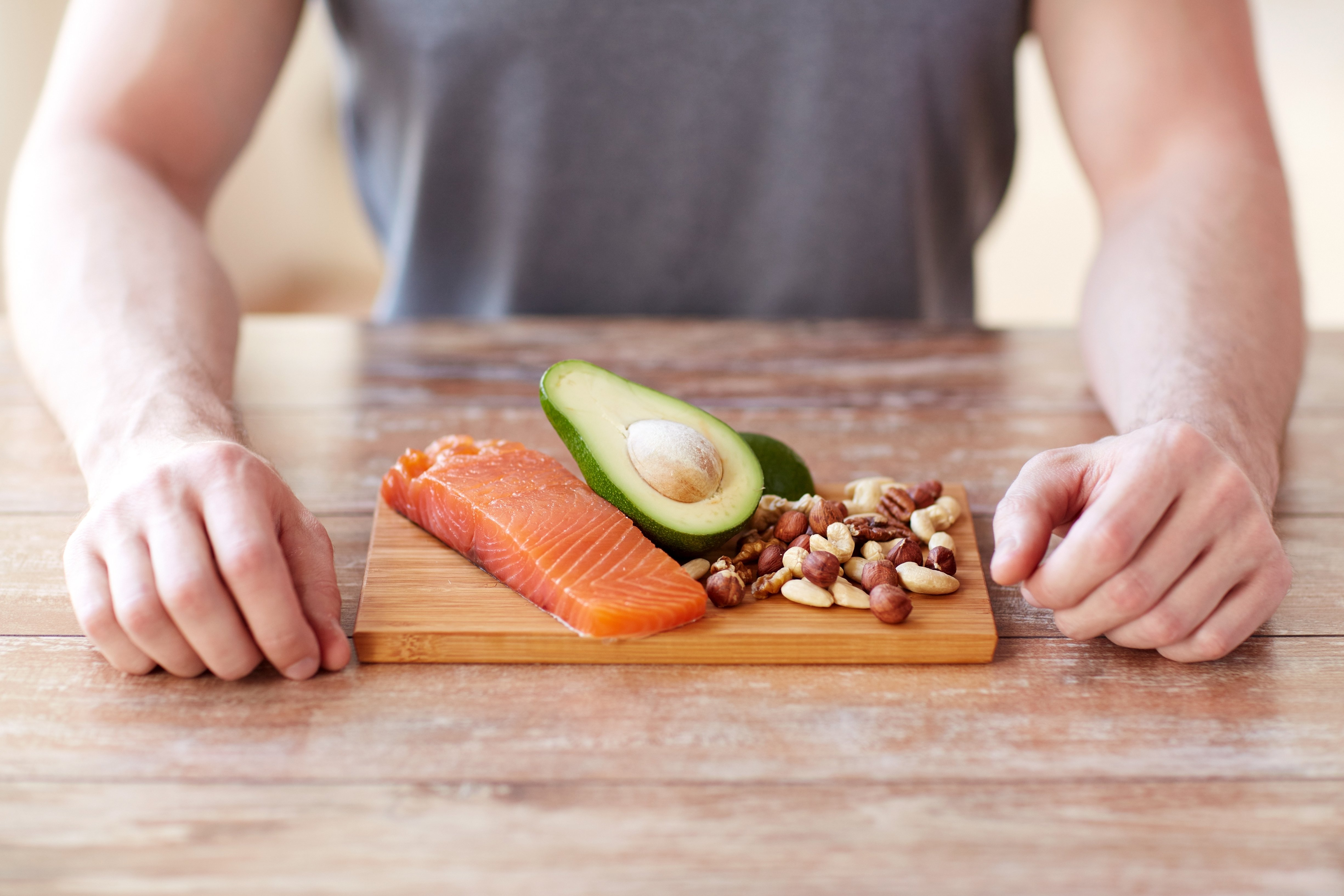 Young man with salmon, avocado, nuts —parts of a paleo diet