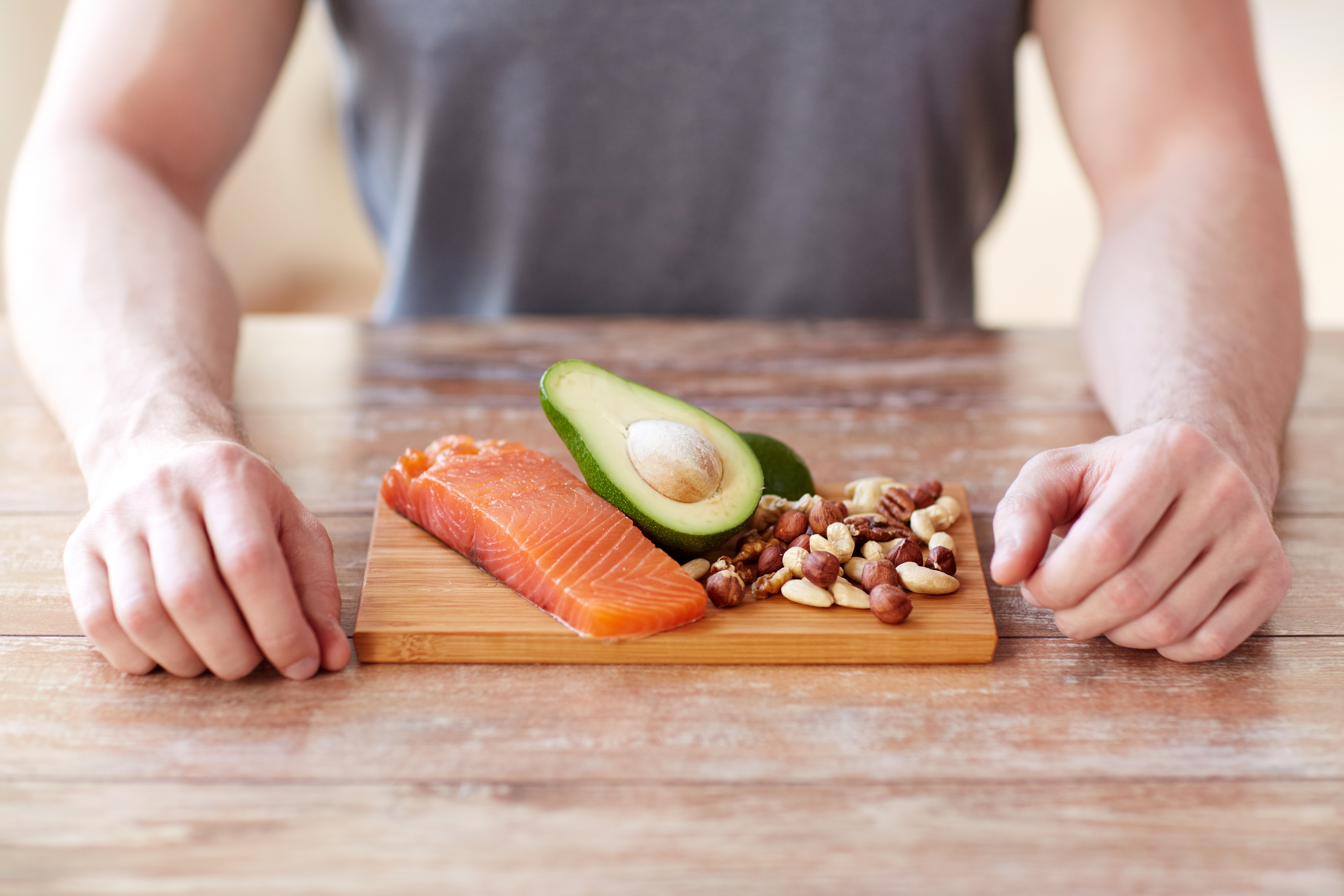Young man with salmon, avocado, nuts — parts of a paleo diet