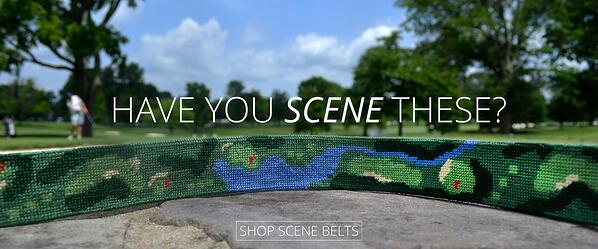 Close-up of a needlepoint belt depicting a golf course with a real golf course in the background.