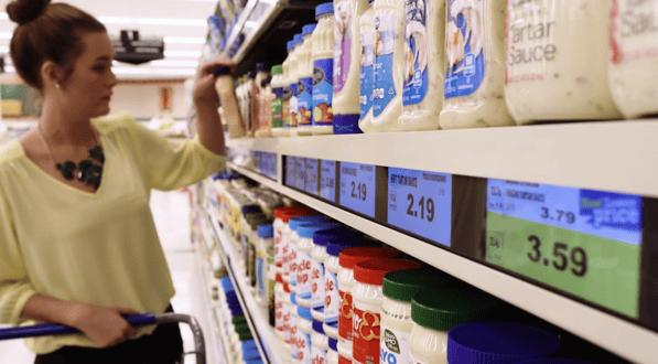 Woman looking at shelves of salad dressings.