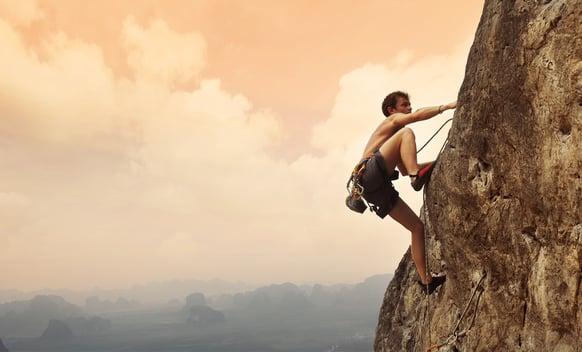 Climber climbing up a mountain.