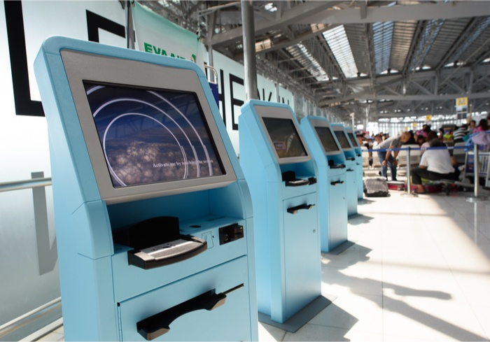 Row of blue kiosks inside of an airport.