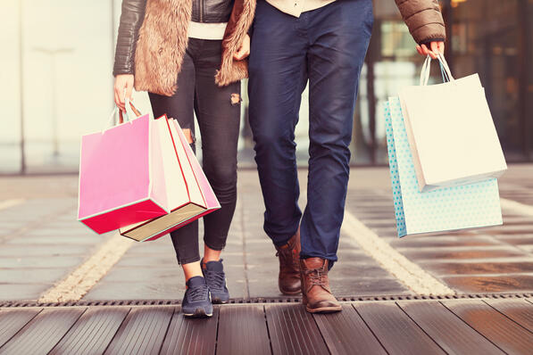 Two shoppers carrying shopping bags.