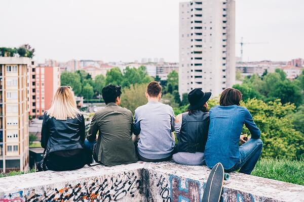Five young people sitting on a wall outside with their backs to the camera.