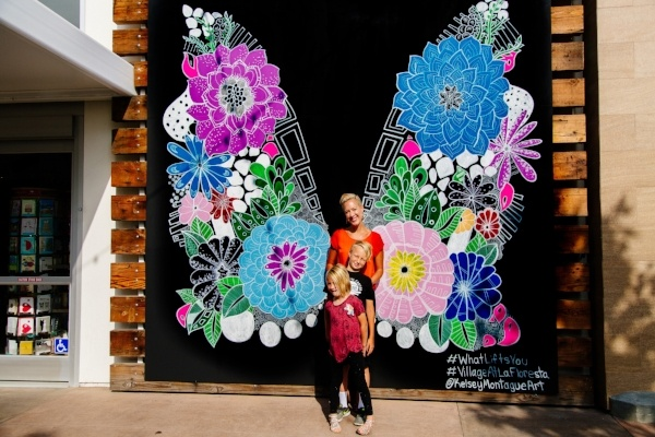 Mural artist posing with her two children in front of a mural of large wings made of flowers.