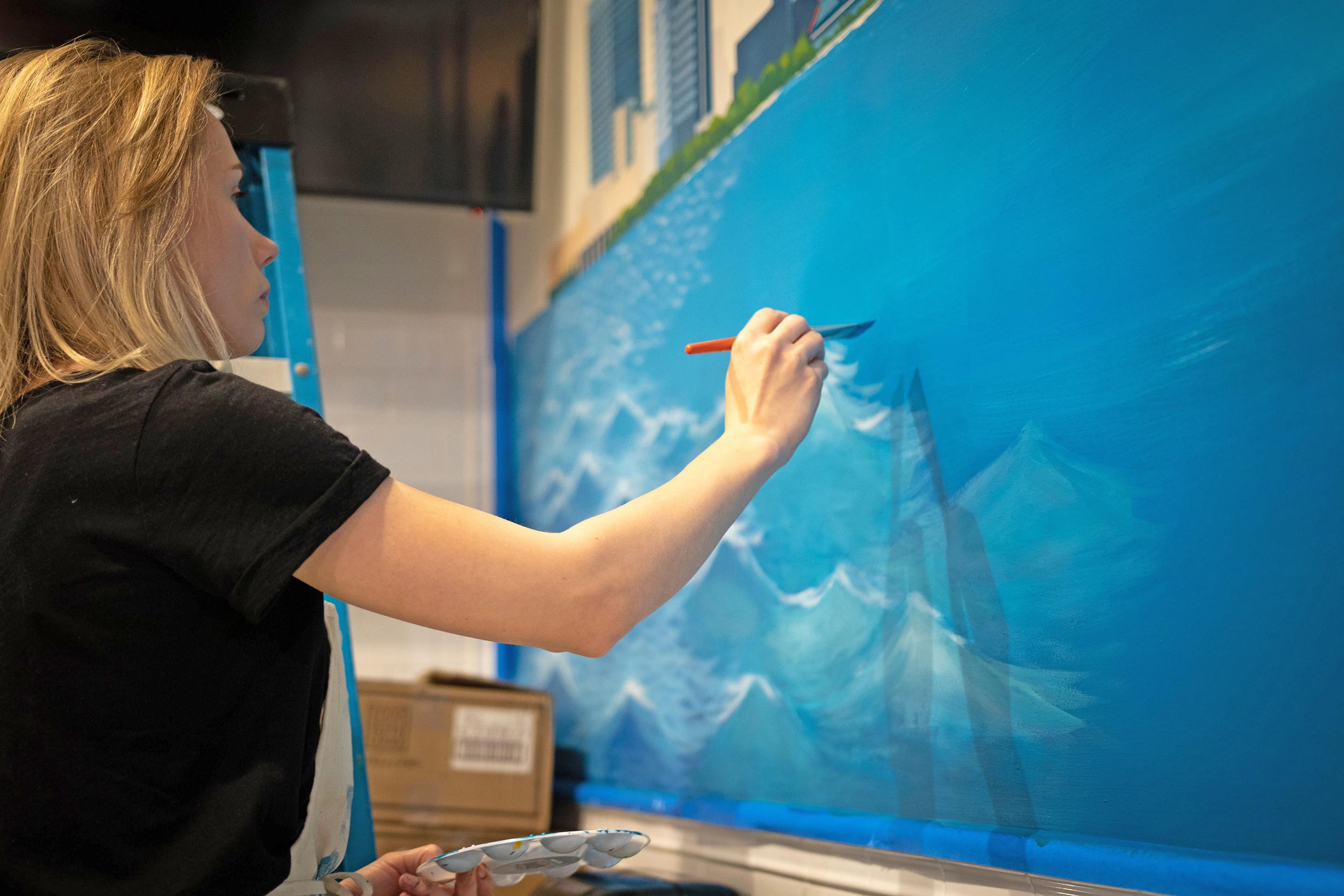 Angelina Kaduk painting an ocean mural