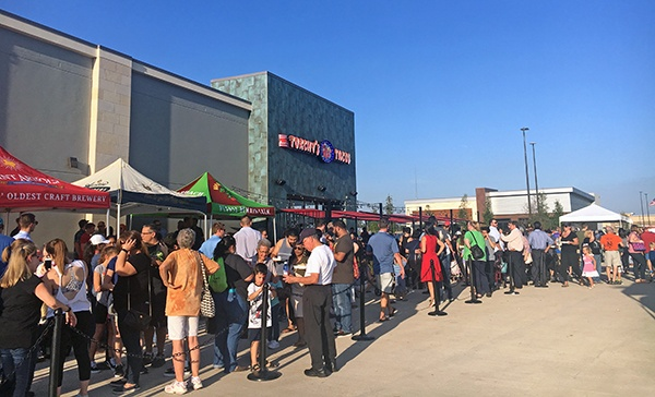 A long line of patrons standing outside Torchy's Tacos on opening day.