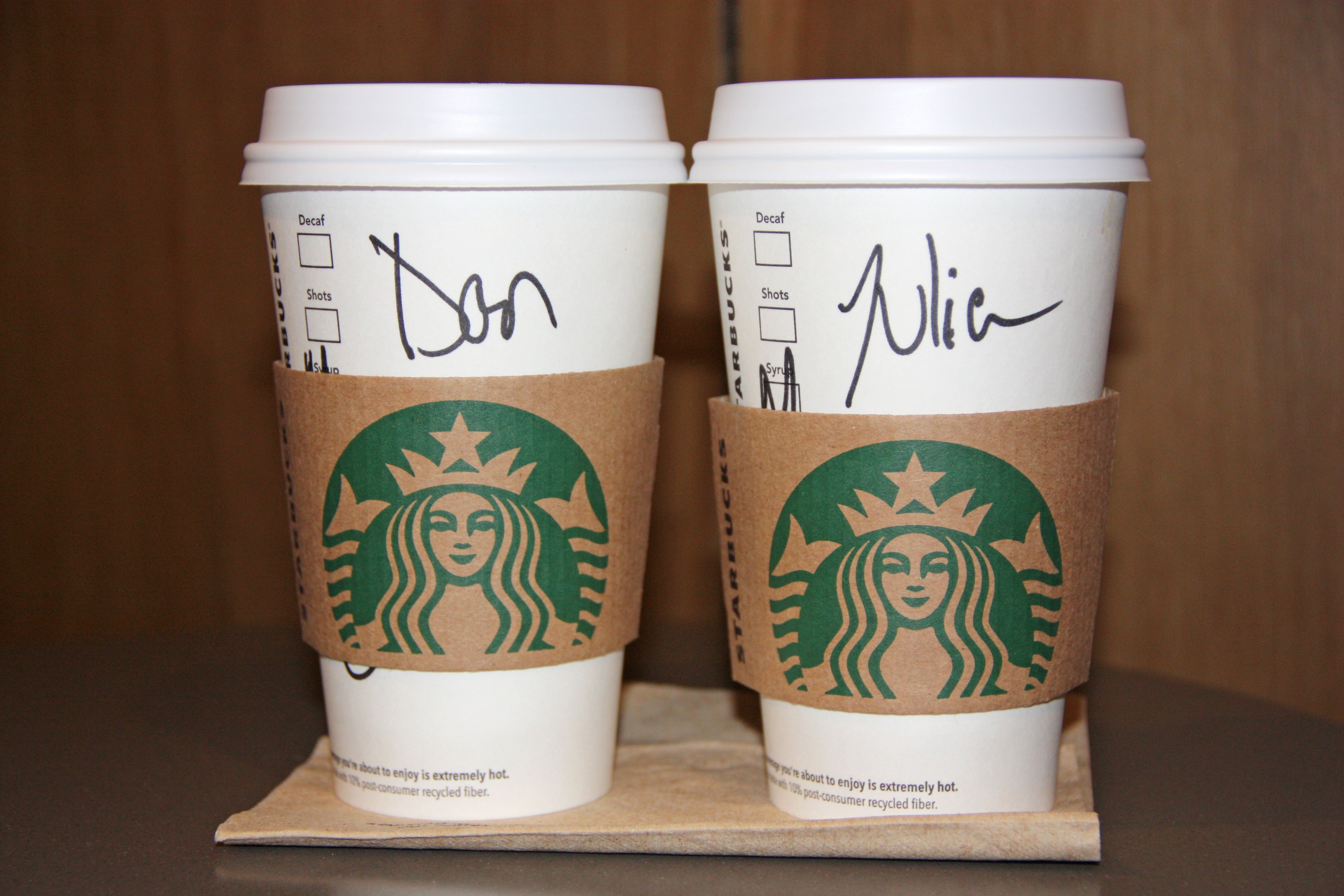 two starbucks hot latte cups with customer name written on them.