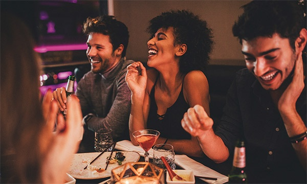 Young people laughing while enjoying drinks and meal.