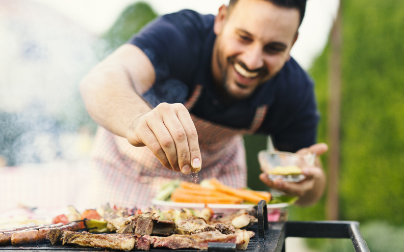 man cooking outside on grill